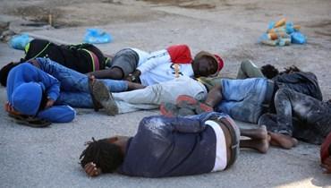 مهاجرون أفارقة أنقذهم الجيش التونسي، يستريحون في ميناء القطيف في بن قردان جنوب تونس (11 حزيران 2021، أ ف ب).