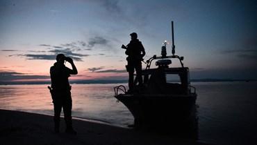 شرطيان يقومان بدورية في دلتا نهر إيفروس على طول الحدود اليونانية التركية (8 حزيران 2021، أ ف ب).