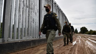 شرطيون يونانيون يقومون بدورية عند السياج الفولاذي الممتد على طول نهر إيفروس بالقرب من قرية بوروس (8 حزيران 2021، أ ف ب).