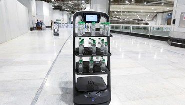 بالصور- حرصاً على التباعد الاجتماعي... روبوتات لتوزيع مياه زمزم على زوار مكة المكرمة