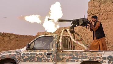 """عنصر من ميليشيا """"سانغوريان"""" المناهضة لـ""""طالبان"""" يطلق النار من مدفع رشاش ثقيل خلال قتال في قرية مختار بضواحي لشقر جاه- ولاية هلمند (أ ف ب)."""