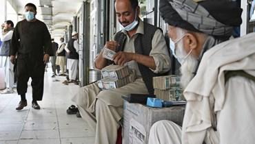 صراف أفغاني يعد دولارات أميركية في سوق شاهزاد للصيرفة في كابول الاثنين.   (أ ف ب)
