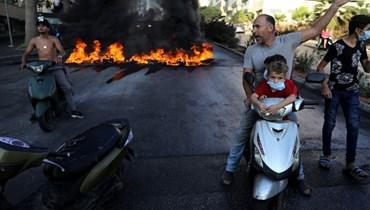 مواطن على دراجته مع طفلين خلال الاحتجاجات (أ ف ب).