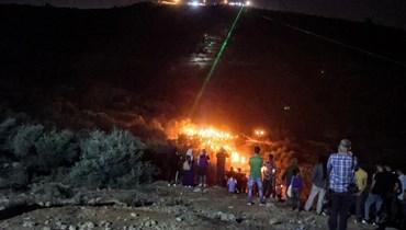 فلسطينيون يستخدمون مشاعل الليزر خلال تظاهرة ليلية في بلدة بيتا  بالقرب من نابلس بالضفة الغربية المحتلة، احتجاجا على بؤرة المستوطنين الإسرائيليين في إفيتار (30 حزيران 2021، أ ف ب).