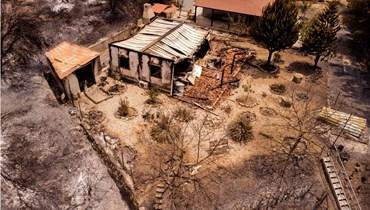صورة جوية تظهر منزلاً محترقا بالقرب من قرية أورا على المنحدرات الجنوبية لجبال ترودوس في جزيرة قبرص (4 تموز 2021، أ ف ب).