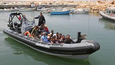 مهاجرون يصلون بالقوارب إلى ميناء القطيف في بن قردان جنوب تونس بعد انقاذهم (27 حزيران 2021، أ ف ب).