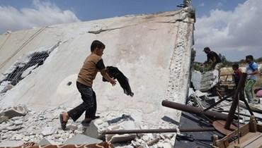 طفل ينقذ متعلقاته من منزل دمره هجوم صاروخي روسي في منطقة جبل الزاوية جنوب محافظة إدلب (أ ف ب).