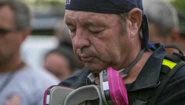 رجل إنقاذ يصلي خلال وقفة صلاة في سورفسايد بولاية فلوريدا (7 تموز 2021، أ ب).