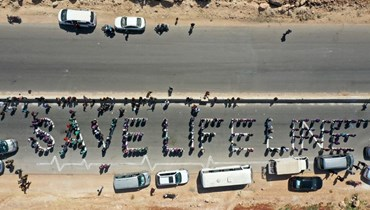 سلسلة بشرية خلال إدخال مساعدات إنسانية من معبر باب الهوى (أ ف ب).
