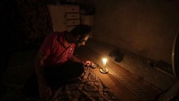 رجل لبناني يدخن سيجارة على ضوء الشموع في العاصمة بيروت (أ ف ب).