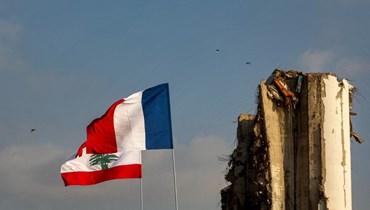 علما لبنان وفرنسا بالقرب من صوامع الحبوب المتضررة في المرفأ (أ ف ب).