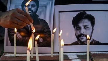 شموع اضاءها صحافيون بالقرب من صور لدانيش صديقي في كولكاتا بالهند (16 تموز 2021، أ ف ب).