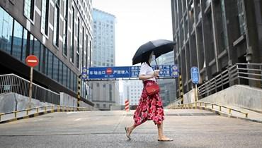 امرأة تمرّ بالقرب من مبنى إداري في بيجينغ (15 تموز 2021، أ ف ب).