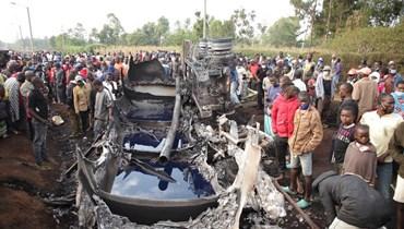 اشخاص تجمعوا حول شاحنة صهريج محترقة اشتعلت فيها النيران بعدما انقلبت في غرب كينيا (18 تموز 2021، أ ف ب).