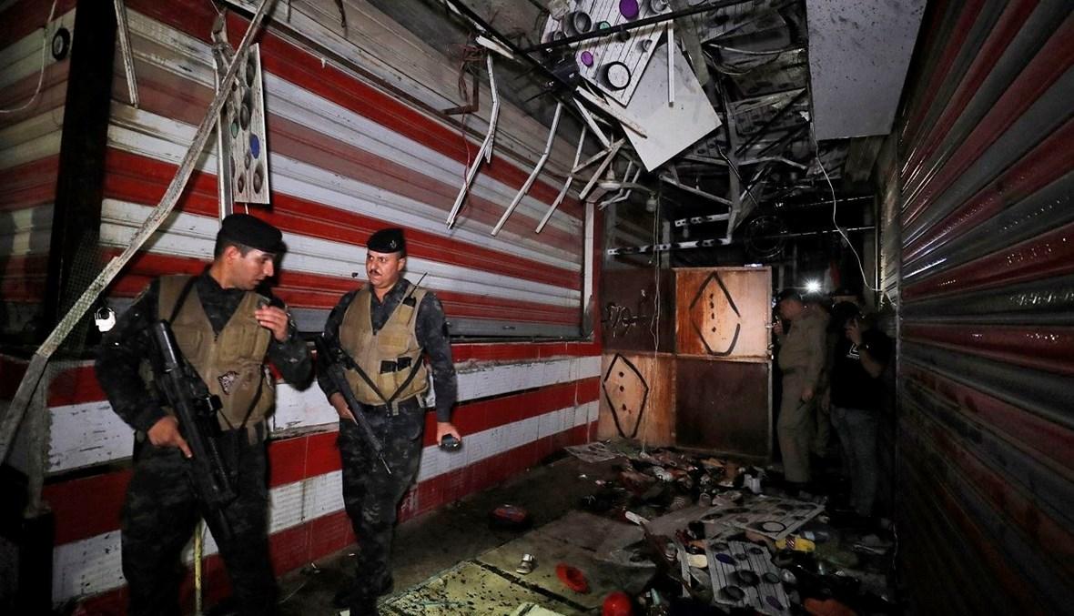 عنصران من قوى الأمن العراقية يتفقّدان موقع التفجير في السوق الشعبي بمدينة الصدر (أ ف ب).