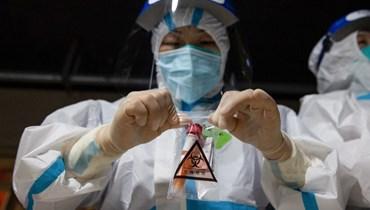 عامل طبيً يجمع عينة من اختبار الحمض النووي لفيروس كورونا (أ ف ب).