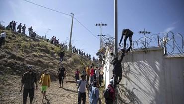 أشخاص يتسلقون سياجًا في المنطقة الواقعة على الحدود الإسبانية -المغربية، خارج جيب سبتة الإسباني (18 ايار 2021، أ ب).