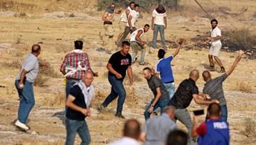 متظاهرون فلسطينيون يشتبكون مع مستوطنين إسرائيليين في معسكر للجيش الإسرائيلي تم إخلاؤه بالقرب من حاجز تياسير شرق طوباس شمال الضفة الغربية المحتلة (24 تموز 2021، أ ف ب).
