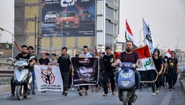 متظاهرون يرفعون لافتات احتجاجية في ساحة الحبوبي بمدينة الناصرية جنوب العراق، تطالب بمحاسبة قتلة عشرات النشطاء (18 تموز 2021، أ ف ب).