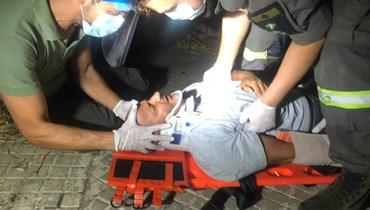 عناصر الدفاع المدني خلال إسعافهم الزميل المصوّر حسام شبارو بعد الاعتداء عليه في محيط عين التينة (نبيل اسماعيل).