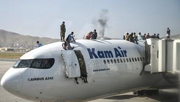 مواطنون أفغان يتسلّقون طائرة في مطار كابول (أ ف ب).