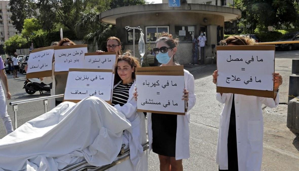 """صيدلي يجلس على نقالة يحمل لافتة كتب عليها """"لا بنزين = لا سيارة إسعاف"""" (أ ف ب)."""