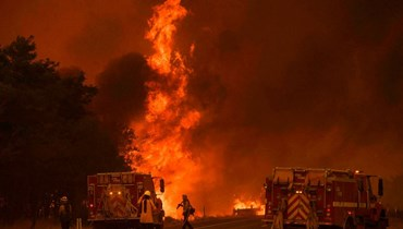 """رجال إطفاء يحاولون إخماد حريق """"ديكسي فاير"""" قرب ميلفورد في كاليفورنيا (أ ف ب)."""