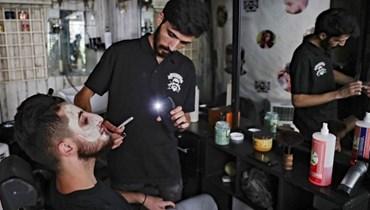 حلاق يستخدم المصباح اليدوي على هاتفه وهو يحلق شعر زبون في متجره في منطقة الحمرا (أ  ف ب).