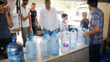 """تعبئة غالونات مياه بعد تحذير """"اليونيسف"""" (حسن عسل)."""