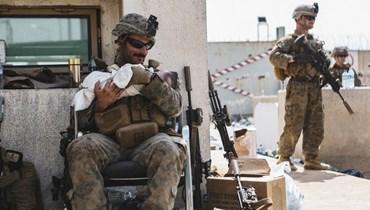 جنديّ أميركي يحمل طفلاً خلال إجلاء الإفغان من كابول (أ ف ب).