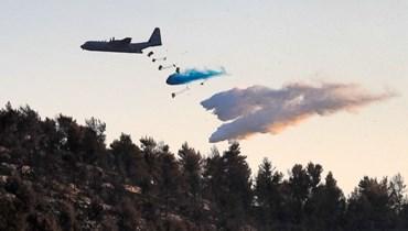 صورة تعبيرية- طائرة تقذف مواد مانعة للحريق خلال إخماد نيران مندلعة في غابة بالقرب من كيبوتس تسوفا غرب القدس (17 آب 2021ـ أ ف ب).