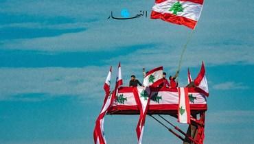 لبنانيون يلوّحون بالعلم اللبناني (تعبيرية- نبيل إسماعيل).