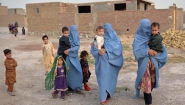 """أفراد من عائلات فرّت من القتال الدائر في إقليم بادغيس بين القوات الحكومية ومقاتلي """"طالبان"""" (أ ف ب)."""