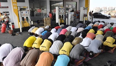 """شيخ يؤمّ صلاة الجمعة في باحة محطة """"كورال"""" - الجية (نبيل إسماعيل)."""