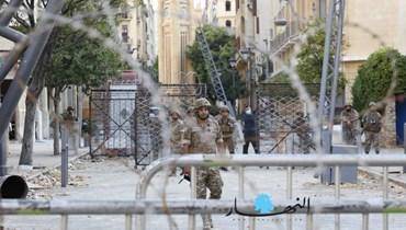 عناصر من الجيش وراء الشريط الشائك أمام أحد مداخل المجلس النيابي في بيروت.