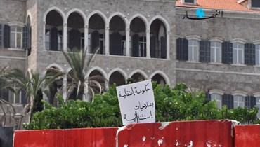 """لافتة وضعها محتجّون على الحائط الفاصل أمام السرايا الحكومية تطالب بـ""""حكومة انتقالية بصلاحيات استثنائية"""" (تعبيرية- نبيل إسماعيل)."""