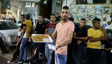 شاب فلسطيني يوزع الحلوى ابتهاجاً بفرار ستة معتقلين أمنيين من سجن جلبوع (أ ف ب).