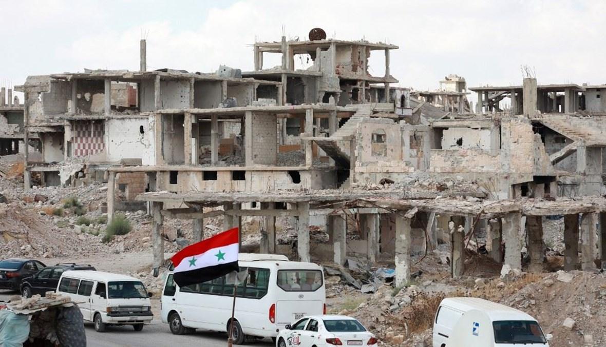 العلم السوري في درعا (أ ف ب).