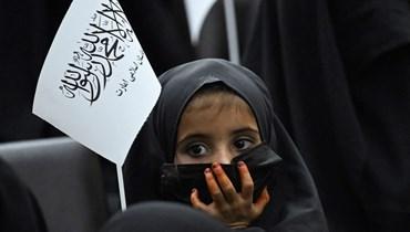 """فتاة ترفع علم """"طالبان"""" خلال تجمّع لطالبات مؤيدات للحركة في جامعة رباني التعليمية في كابول (أ ف ب- 11 أيلول 2021)."""