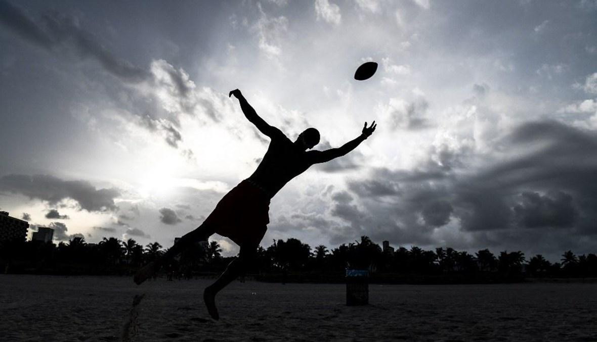 رجل يمسك كرة القدم على الشاطئ في ميامي (أ ف ب).