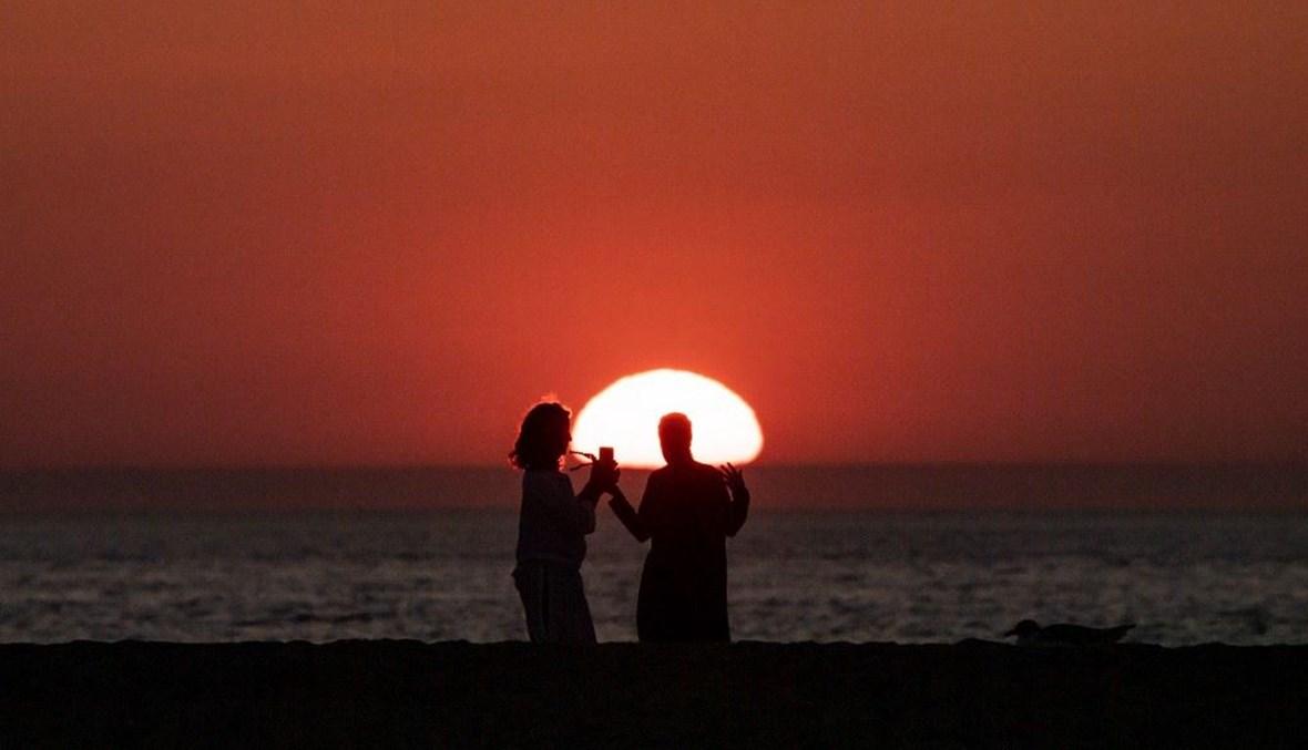 الناس ينظرون إلى غروب الشمس خلال مهرجان دوفيل السينمائي (أ ف ب).