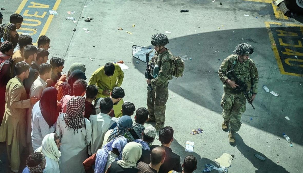 جنود أميركيون تأهبوا، بينما ينتظر أفغان في مطار كابول في كابول (أ ف ب).