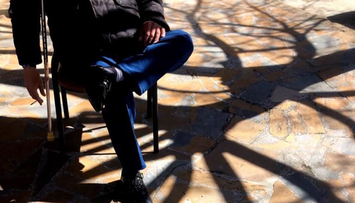 """""""أعود إلى كرسيّ حديديّ بلا يدين لنمسكهما عندما يقسو الكلام"""" (الصورة لسميح زعتر)."""