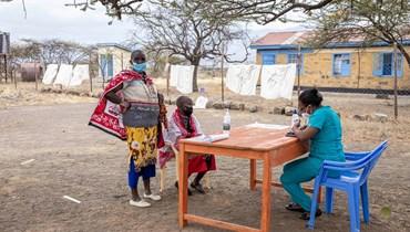 امرأتان من قبيلة الماساي تسجلان اسميهما لتلقي لقاح كورونا في مستوصف اولتيبيسي في كاجيادو بكينيا (9 أيلول 2021، أ ف ب).