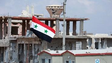 علم سوري فوق أبنية متضرّرة في منطقة درعا البلد التابعة لمدينة درعا جنوب سوريا (تعبيرية- أ ف ب).