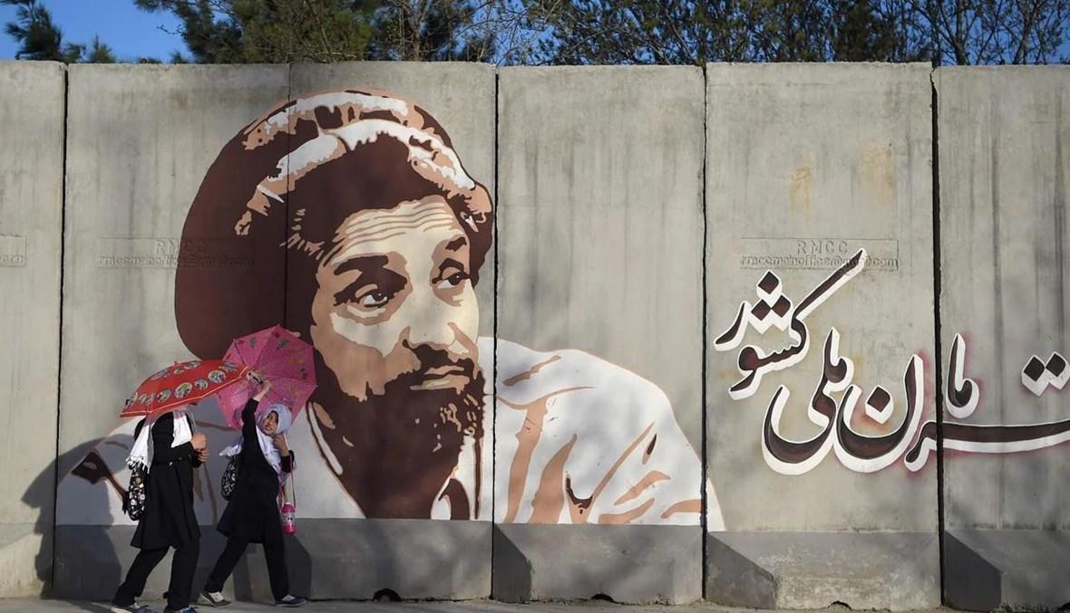 """جدارية تمثّل القائد الأفغاني الراحل أحمد شاه مسعود مع عبارة """"مسعود بطل أمتنا"""" في العاصمة الأفغانية كابول. (أ ف ب)."""