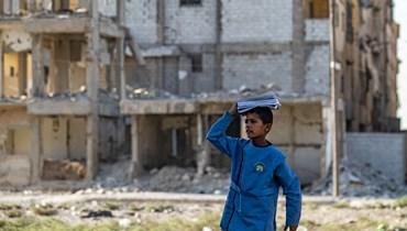 طالب سوري يمر قرب مبان متضررة في مدينة الرقة الشمالية خلال توجهه الى المدرسة (23 ايلول 2021، ا ف ب).