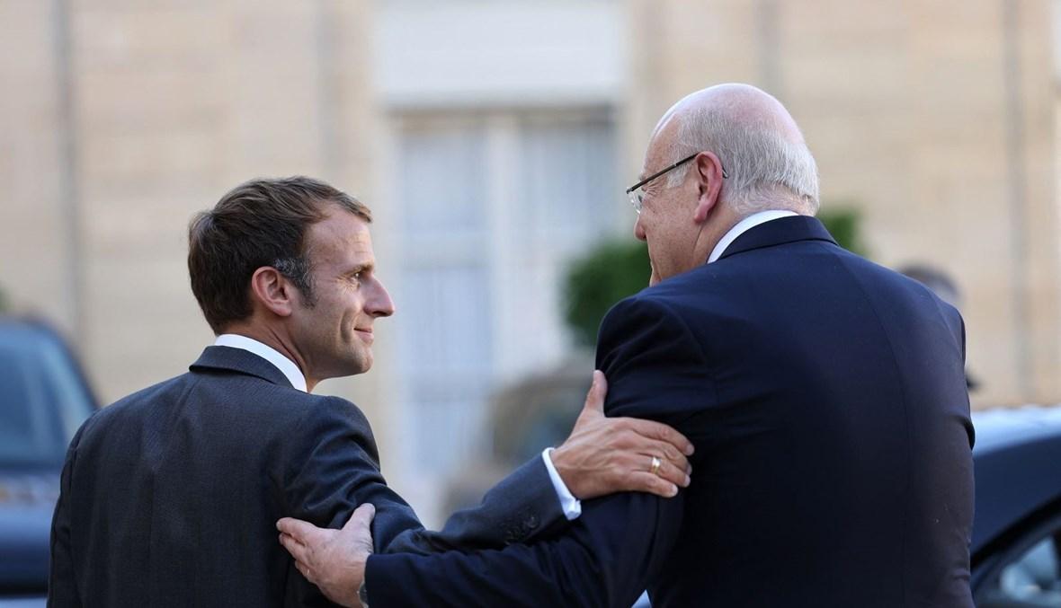 الرئيس الفرنسي إيمانويل ماكرون والرئيس نجيب ميقاتي في باحة قصر الإليزيه في باريس (أ ف ب).