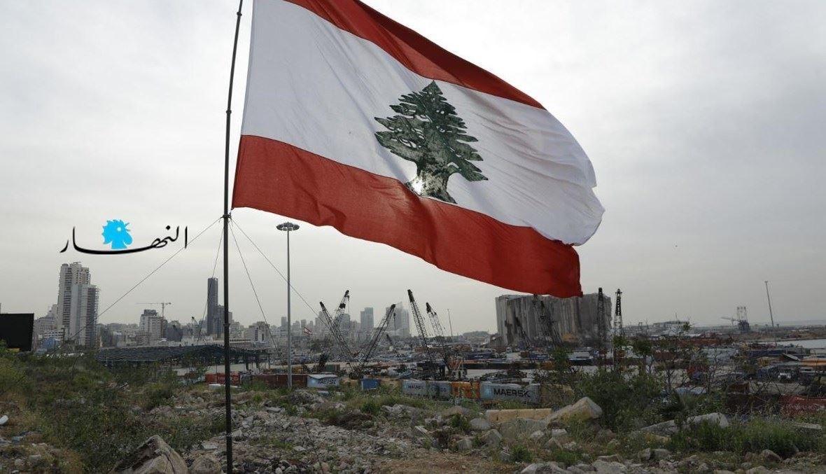 العلم اللبناني مقابل أهراءات القمح في مرفأ بيروت المدمّر (مارك فياض).
