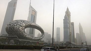 سيارات تسير في شارع الشيخ زايد في دبي خلال عاصفة رملية، 24 أيلول 2021 (تعبيرية- أ ف ب).